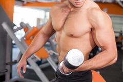 Cheerful young male sportsman is training in fitness center - stock photo