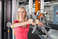 Cheerful fit girl is exercising with the equipment in gym Stock Photos