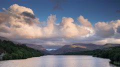 4k time lapse of cumulus clouds over lake & mountains at sunset, Wales Stock Footage