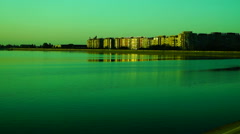 Urban landscape with lake at sunset, pan Stock Footage