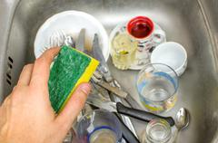 chores, washing dishes in the sink with sponge in hand - stock photo