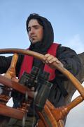Young sailor on a ship's deck behind a steering wheel Stock Photos