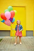 Happy little girl outdoors with balloons Stock Photos