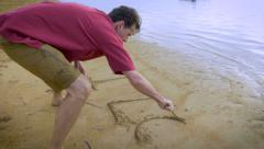 Attractive man writes I Love You in the sand on the beach with a stick Stock Footage