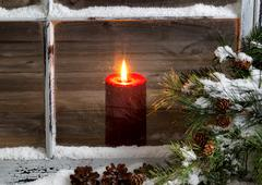Christmas red candle with snow covered home window and pine trees - stock photo
