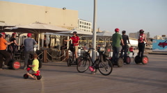 People on segways ignore war siren drill in Tel-Aviv port, - stock footage