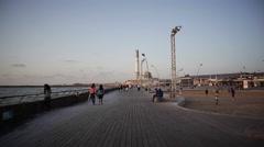 Woman walks with crutches in Tel-Aviv port boardwalk, power station - stock footage