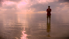 Man stands in calm water of ocean praying during sunrise Stock Footage