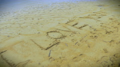 "Fly over shot of ""I Love You"" written in the sand on the beach - stock footage"