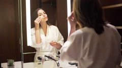 Woman cleaning face with cotton swab in front of the mirror HD Stock Footage