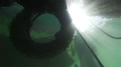 Stock Video Footage of Sun rays penetrate through spectacular tire of the truck under water