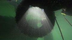 Sun rays penetrate through spectacular tire of the truck under water Stock Footage