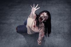 Female zombie crouching on the floor Stock Photos