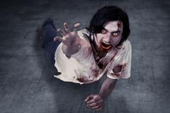 Male zombie crouching on the floor - stock photo