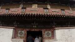 People crowded in the doorway of an old Buddhist temples of the ancient monaster Stock Footage