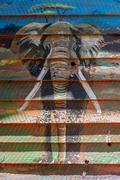Elephant mural on wooden shack in sunshine - stock photo