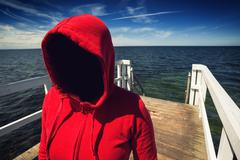 Faceless Hooded Unrecognizable Woman at Ocean Pier, Abduction Concept - stock photo