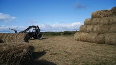 Tractor loading hay bales during agricultural works Stock Footage