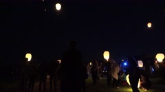 People flying shining sky lamp in the sky at night. 4K Stock Footage