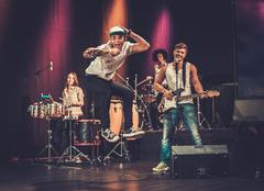 Multiracial music band performing on a stage Stock Photos