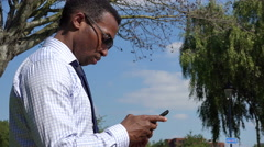 Handsome Black Man using smatphone at park - stock footage