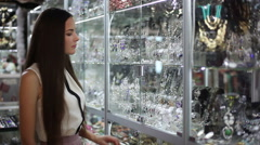 Young woman is choosing jewelry in the shop - stock footage