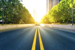 Bi-directional road with the doubled solid lines under sunshine Stock Photos