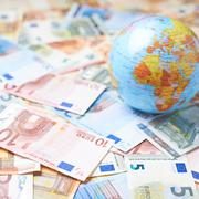 Earth globe over the pile of money - stock photo