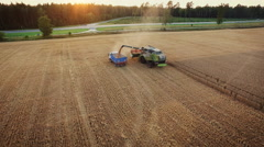 Aerial drone shot of a combine harvester loading a truck in a field at sunset Stock Footage