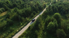 Aerial drone shot of a moving suv car on a road in forest Stock Footage