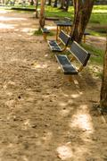 Stock Photo of Bench with nobody in park illustrating empty concept.