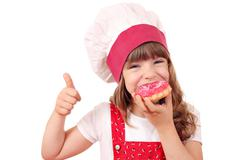 hungry little girl cook eat sweet donuts - stock photo