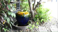 Overflow water decorative jar in the garden - stock footage
