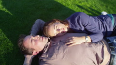 4K Attractive romantic couple lying down together on the grass - stock footage
