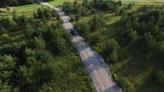 Aerial drone shot of a moving suv car on a road in forest - stock footage