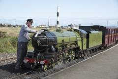 Engine driver polishing the Green Goddess loco which operates a passenger ser - stock photo