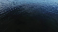 Aerial drone shot of sea with light waves in the evening Arkistovideo