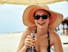 Beautiful girl in wide-brimmed hat drinking champagne Stock Photos