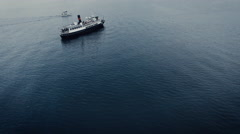 Aerial drone shot of vintage cruise ferry and a small sailing boat in the sea - stock footage