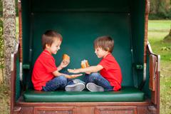 Two kids, sitting in a sheltered bench, playing hand clapping game and eating Stock Photos