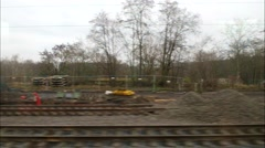 Horizontal movement from train window with excavators at construction zone Stock Footage