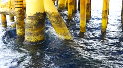 Stock Video Footage of Waves Hit Surface Casing of Producing Platform Facility at Offshore