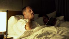 Couple in bed at night, man using tablet computer and going to sleep - stock footage