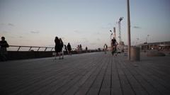 Man cycles at Tel-Aviv port boardwalk towards power station - stock footage