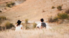 Couple sitting on the grass and looking at the hills Stock Footage