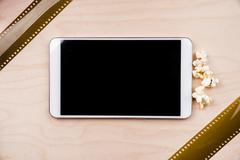 Tablet pc on dark background with attributes of cinema - stock photo