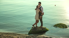 Stylish couple standing on the rocks on the shore Stock Footage