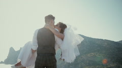 Fiance holds his bride in his arms on the cliff Stock Footage