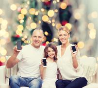 Happy family with smartphones Stock Photos