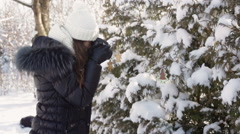 Woman in winter clothing and knitted white hat photographing forest Stock Footage